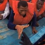 """Migrants on wooden boat being rescued by """"Save the Children"""" NGO crew from the ship Vos Hestia in the Mediterranean sea off Libya coast"""
