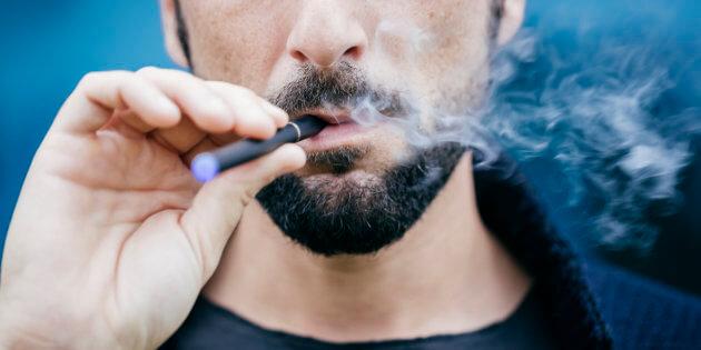 Un homme fumant du E-cigarette.